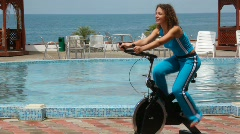 Happy young woman training on exercise bicycle, pool and sea Stock Footage