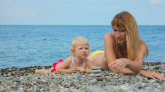 Mother building stone stacks with little daughter in beach Stock Footage