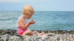 Little girl sitting on pebble beach and playing with stones Stock Footage