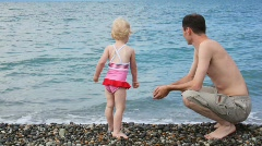 Man with his little daughter throwing pebbles to sea in pebble beach Stock Footage