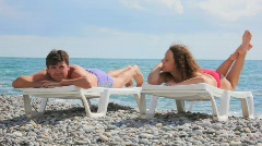 Couple lying on beach beds in pebble beach, sea and clouds Stock Footage
