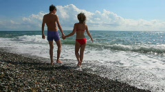 Young caucasian couple has fun in sea surf, clouds in background Stock Footage
