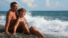 Happy couple sitting on pebble beach, sea surf in background Stock Footage