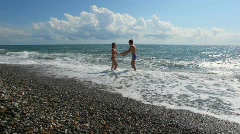 Young couple has fun in sea surf, clouds in background Stock Footage