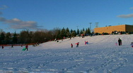 Families and children sledding down hill Stock Footage