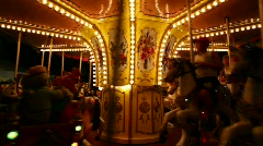 Kids on carousel merry-go-round amusement ride with galloping horses Stock Footage