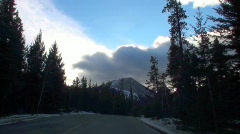 Bow valley mountains trees clouds driver perspective Stock Footage