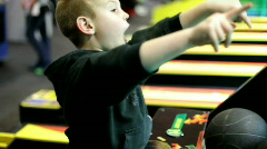 Boy Playing Basketball Game at Arcade Stock Footage