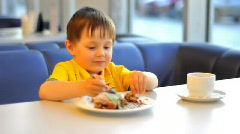 Boy eat cake in cafe - stock footage