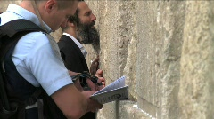Western Wall - a police man and jewish man are praying Stock Footage
