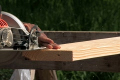 Carpenter sawing lumber with power saw  Stock Footage