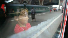 Little girl straightening curtains on the train window Stock Footage