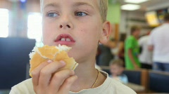 Boy eating hamburger at fast food cafe Stock Footage