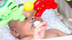Baby laying in the crib with toys Stock Footage