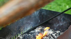 Putting out flame in the grill with the stick Stock Footage