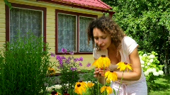 Yang woman smelling yellow Echinacea flowers Stock Footage