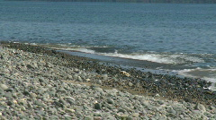 Little ocean swell rolling slowly and relaxing towards a pebble stone beach Stock Footage
