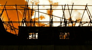 Amber sky floating past derelict building scaffolding Stock Footage