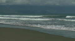 Ocean waves rolling towards the beach with dark clouds in the background - stock footage