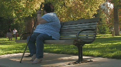 Obese woman on park bench Stock Footage