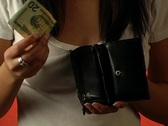 Stock Video Footage of Beautiful Young Woman Puts a Twenty-dollar Bill in her Wallet (close-up)
