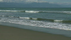 Small waves rolling towards the sandy beach Stock Footage