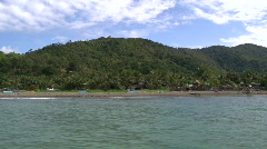 Camera on a boat driving along the coast with hills covered in lush green forest Stock Footage