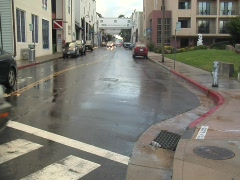 Zoom in from Cannery Row to reveal plastic bottle in storm drain Stock Footage