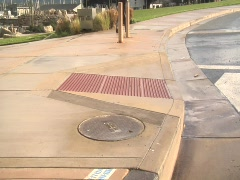 Tilt down to reveal trashy storm drain Stock Footage
