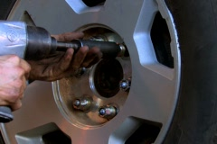 Mechanic tightening lug nuts with torque wrench Stock Footage