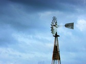 Old farm windmill surrounded by storm clouds Stock Footage