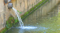 HD Water flowing from the pipe into town river Stock Footage