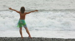 young woman standing on pebble beach against waves of sea - stock footage