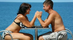 Man and woman in swimsuit sits at table, join hands, sea in background Stock Footage