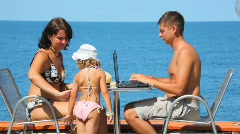 Woman spreading tanner on her little daughter, man working on notebook Stock Footage