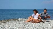 Sitting woman and man with notebook get up in rocky beach Stock Footage