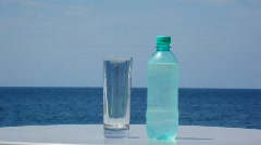 Bottle of cold water and glass standing on table, sea in background Stock Footage