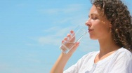 Beautiful young woman drinks water from glass, blue sky in background Stock Footage