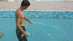 Boy with water hose and sponge cleaning swimming water pool Stock Footage