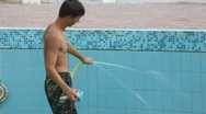 Stock Video Footage of boy with water hose and sponge cleaning swimming water pool