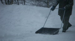 Man shoveling snow while snow is falling. Stock Footage