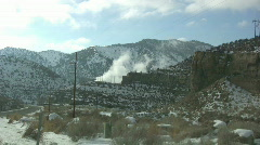 Smoke comes up from the powerline infested hills Stock Footage