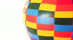 Part of coloured toy air ball revolves fast on white background Stock Footage