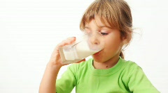 Small girl drinks milk from glass and starts up bubbles in it Stock Footage