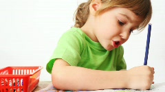 Small girl sits at table, paints by pencil picture and talk Stock Footage