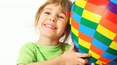 Girl embraces toy varicoloured air ball and smile on white background Stock Footage