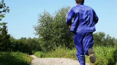 Man in turn blue gym suits runs back on lane in park in summer Stock Footage
