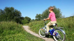 Small boy in pink vest goes forward on blue bicycle in park in summer Stock Footage