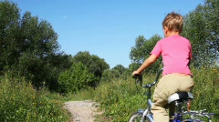 Small boy in pink t-shirt goes forward on blue bicycle on footpath in park Stock Footage