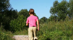 Small boy in pink t-shirt runs there here in park in summer Stock Footage
